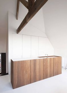 Kitchen with wooden cooking islang + minimal white cabinets + original wooden beams. House GS by Graux & Baeyens in Belgium.