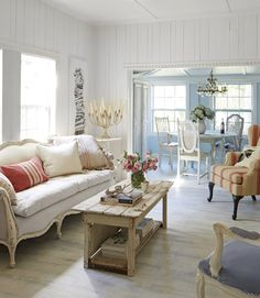 Think every living room needs draperies? Think again. Here, bare windows make for a refreshingly streamlined look that also takes advantage of this Florida cottage's beautiful light.   - CountryLiving.com