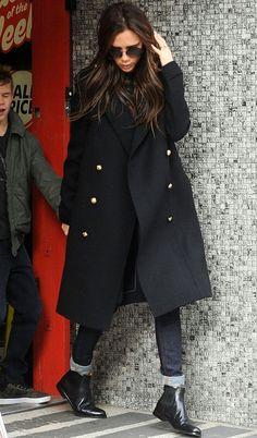 Виктория Бекхэм в сапогах и черном пальто в стиле милитари
