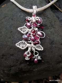 This sterling pendant is red, garnet and pink in color and is made to resemble a grape vine. Sterling wire has been wrapped to make leaves of this vine pendant. The top of the structure is decorated with garnets, pearls, and swarvoski crystals. The structure of the pendant is made of silver filled wire. The pendant is about two and a half inches from the top of the bail to the bottom of the bangles. The widest point is about an inch and a half. The bangles like the rest …