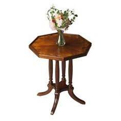 Octagonal accent table with carved fluted columns.      Product: Accent table  Construction Material: Select hardwoods and wood products  Color: Cherry  Features:   Octagonal-shaped top  Raised edges  Outer border of Mappa burl veneer  Dimensions: 26.75 H x 22.25 W x 22.25 D       Note: Assembly required