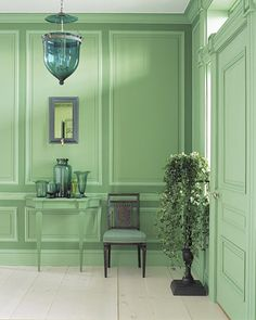 Fresh Greens  In an entry hall, green becomes a link between outside and in. Three different tones accentuate the paneling; the console is painted to match. The hanging lamp, glass vessels, and sconce's mirror are also in varying shades of green. Even in such abundance, this color is calming.  -- Martha Stewart Living, September 2003