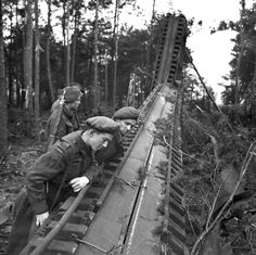Personnel of the Royal Canadian Artillery, examining a damaged German V-1 flying bomb launching ramp, Almelo, Netherlands, 5 April 1945