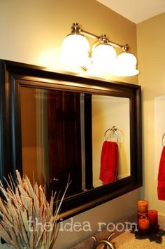 Framing around an old bathroom mirror and updating your light fixture can only add value to your house!  #housestaging