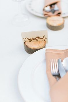 Make a slit into a log slice and insert the place card | Brides.com