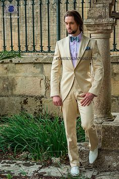 Beige short-tailed suit in 'Alta Moda Solbiati' cotton satin fabric, with peak lapel, single corozo button closure and single vent at back, style 1039 Ottavio Nuccio Gala, 2015 Fashion Collection.