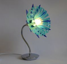 UK-based Sarah Turner uses plastic bottles, among other materials, and transforms them into items you would never have guessed were made from recyclables. Water Bottle Crafts, Plastic Bottle Flowers, Plastic Bottle Crafts, Recycle Plastic Bottles, Plastic Craft, Table Lamp Shades, Table Lamps, Recycled Bottles, Lamp Bases