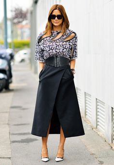 Christine Centenera wears a cutout top with a belted midi skirt and pumps