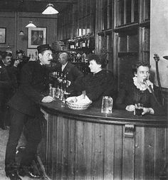 Circa 1880s. Interior of a barroom in London. The lady on the right is using a speaking-tube, presumably to talk to the kitchen.