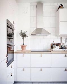 Vitt kök med bänk i ljust trä.