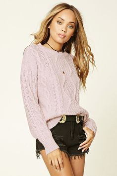 A loose cable knit sweater with a round neckline and long sleeves.