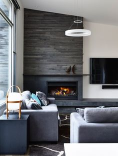 Fireplace in solid colorblock column with two textures - smooth at the bottom, something like stacked stone above.