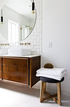 MASTER BATH: good for a smaller nook. gigantor, circular mirror mounted on feature wall of fun tiles + flanking mod pendants + excellent wall-mount cross-shaped faucets + lovely floating vanity + bright, neutral tones