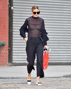 It all meshes: The 30-year-old fashionista blended her sheer ruffled top with pin-striped black trousers