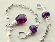 Sterling silver bracelet with 3 beautiful faceted deep red garnets.