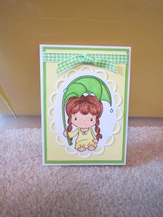 """Card made using CC Designs """"Rainy Day Birgitta"""" stamp. Die cut oval, attached ribbon and colored with markers."""