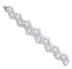 A DIAMOND BRACELET, BY HARRY WINSTON   Designed as a central undulating row of fourteen circular-cut diamonds, weighing from approximately 2.22 to 5.26 carats, spaced and bordered by by marquise-cut diamonds, mounted in platinum, circa 1969, 8 ins., in a Harry Winston black suede case  By Harry Winston, no. 5748
