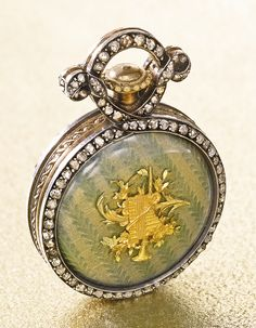 Boucheron - Yellow Gold, Enamel And Diamond-Set Watch, Case Back With Translucent Green And Gray Enamel Over An Engine-Turned Ground, Gilt Musical Trophy To The Center, Diamond-Set Bezels And Bow   c. 1890   -   Sotheby's