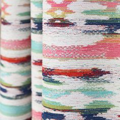 A multi-coloured boho inspired upholstery fabric in candy pink, turquoise, navy blue, grass green, saffron yellow and orange-red and cream.