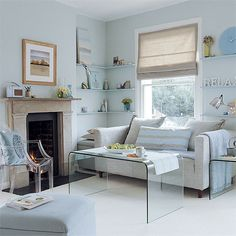 Pale blue and white living room with roman shade and ghost table