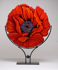 Red Empress Art Glass Sculpture created by Anne Nye. Kiln-formed glass table art. Poppies are a reoccurring theme for the artist. This one is called Red Empress because of its glowing color which Nye lovingly shaded and contoured with finely crushed glass and powder. Kiln fired to 1420 degrees F over a 24-hour period and placed in a powder coated steel stand .