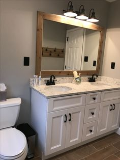 Hall bathroom update Benjamin Moore Coventry gray paint. Rustic wood framed mirror. Wood tile flooring