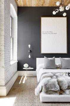 Gray bedroom with faux fur throw and oversized art above headboard