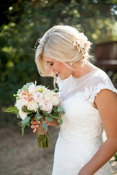 Blushing bride with her flower hair clip and light flowered bouqet | Photographer: Anna Joy Stolz