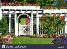 Download this stock image: White garden gate and fence in colorful botanical garden - E0A6GD from Alamy's library of millions of high resolution stock photos, illustrations and vectors.