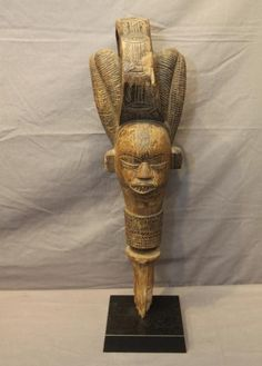KIBE-KIBE DANCE HEAD. Kuyu people, Democratic Republic of Congo. The Kuyu people live on the banks of the Kuyu River in the northwestern part of the country. They are noted for wooden heads such as this which are carried on long wooden poles during initiation ceremonies of the men's secret Ottote Society. The heads typically have an elaborate coiffure and an open mouth revealing fine, sharp teeth. In this instance, the coiffure is divided into two lateral lobes separated by a long band of…