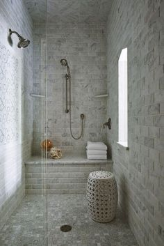 Amazing walk-in shower with Beveled Carrara Marble Subway tiled walls and shower bench. The bathroom features a swirling marble mosaic panel beneath the fixed shower head. The floors are finished in Carrara Marble tile. Two corner marble shelves flank the adjustable shower head over the built-in bench. A pierced white garden stool stands below the showers window and glass shower partition completes the space.