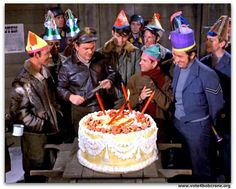 Carter, LeBeau, Newkirk, and many other POW's gather around as Hogan cuts his birthday cake. From the episode ~ Happy Birthday, Dear Hogan