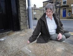 Jenny Oliver with the stone slabs that have been cemented down outside Michelle Champions Hair Design