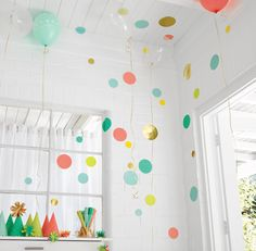Oh Joy! for Target. Circles on wall. Balloons floating with gold ribbon. Party horns in clear hurricane.