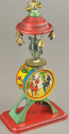 "France, lithographed tin, features one man band, instrument set up with amusing graphics and hand crank allowing sounds and cymbal motions while top spins. 10"" h."