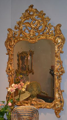 In solid giltwood vigorously carved with flowers and acanthus leaves; the upper pierced cartouche centered by a winged dragon. Circa 1735.