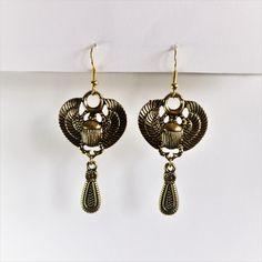 WHITNEY est une paire de boucles d'oreilles en laiton doré avec un pendentif en laiton et  en forme de scarabée égyptien.  Longueur : 6,30 cm Prix : 6,00€  Les boucles d'oreilles sont livrées avec des fermoirs en silicone. Earrings, Jewelry, Shop, Fashion, Egyptian Scarab, Brass Pendant, Lobster Clasp, Boucle D'oreille, Locs
