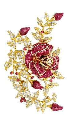A Ruby and Diamond Rose Brooch  Designed as a rose with invisibly-set ruby petals and carved ruby buds, sprinkled with tiny round rubies, to the diamond-set leaves, mounted in 18k gold