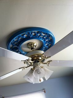 This is the outside frame of a broken clock I got for $10. I took the clock out, spray painted it with 1 1/2 cans Valspar spray paint and hung it on the ceiling with long screws. I took off the fan blades in order to get it on. Cheap, custom ceiling medallion.