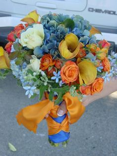 {Colorful Bouquet With: Blue Hydrangea, Blue Forget-Me-Nots, Ivory Roses, Orange Ranunculus, Orange Tea Roses, Large Yellow Calla Lilies, & Green Foliage}
