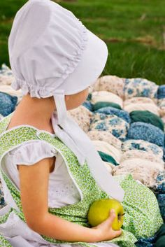 amish child sitting on Amish quilt
