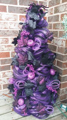 Halloween tree made...purple/black mesh wrapped around tomato cage, wired with purple lights and decorated with garland, tubing, spiders, etc.