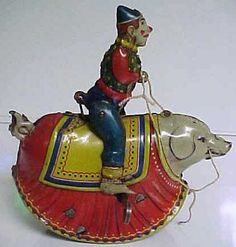 """Circa 1910. CLOWN RIDING PIG EARLY WIND-UP TIN TOY. We can not find any marking on it but it is almost certainly German. When wound the toy rocks back and forth like a bucking bronco. Multi-color litho is nice and bright on side but very lightly faded on other. 100% original. Measures 5"""" in both length and height. Fabulous colors. This is a very early toy in fabulous condition"""