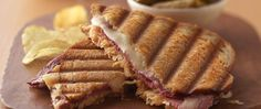 A mouthwatering classic—corned beef piled on top of tangy sauerkraut, with Thousand Island dressing and melted Swiss cheese grilled on rye bread. Pressed Sandwich, Corned Beef Recipes, My Favorite Food, Soup And Sandwich, Sandwich Recipes, Lunch Recipes, Kabob Recipes, Cookbook Recipes, Easy Recipes