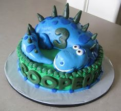How cute is this adorable blue dinosaur birthday cake .