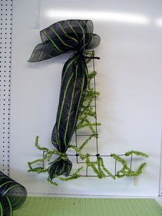 Witch Hat with Legs - tutorial on the Trendy Tree Blog ....made with Deco Poly Mesh, Ribbon Pencil Rails, RAZ Witch Legs ...see more images and instructions http://www.trendytree.com/blog/tutorial-for-deco-poly-mesh-witch-hat-with-dangling-raz-witch-legs/
