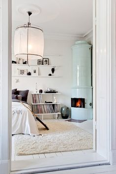 What a cool, minimalistic Scandinavian bedroom. Love that fire feature against the rug and white walls.