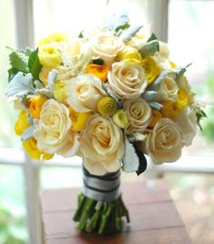 Cream, yellow, and grey wedding bouquet with roses, ranunculus, craspedia, and dusty miller.