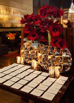 Large blooms in metallic sculpted vases offset these square escort cards, which are laid on a reflective black surface.