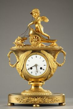 An exceptional gilt bronze mantel clock with its key depicting a winged putto in an antique chariot pulled by two doves resting on a platform adorned with water leaves. The...